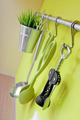 kitchen utensils hanging on green wall
