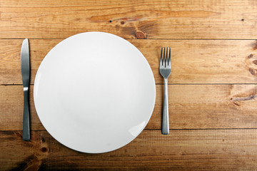 empty white plate on brown wooden table