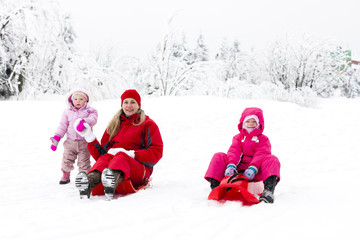 mother and her little daughters with bobs in snow