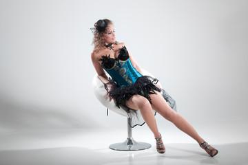 Junge Frau im Burlesque Style posiert sexy auf Hocker