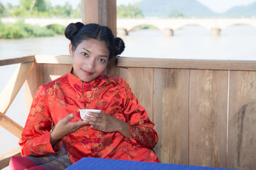Asian woman drinking from a cup