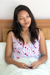 Young woman listening to music player in bed
