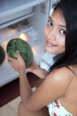 young woman holding a watermelon beside fridge