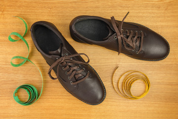 New mens shoes and measuring tapes on wooden polished background