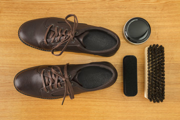 Men's shoes and shoecare accessories on wooden background