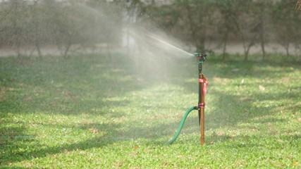 Water sprinkler spraying water over the grass in the garden