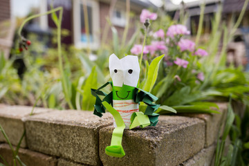 Happy paper frog sitting in the garden on bricks