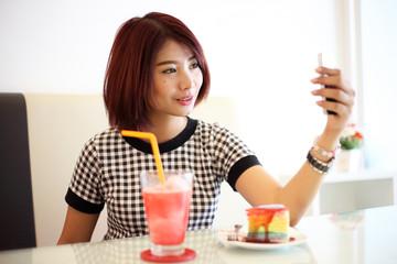 young asian woman taking selfie in coffee shop.