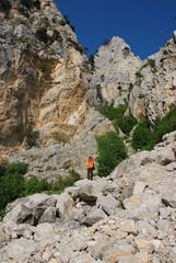 Мужчина на каменной глыбе на фоне высоких скал
