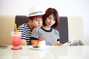 young asian couple reading book in cafe