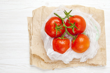 fresh ripe large wet tomatoes in plastic bag on a white wooden b