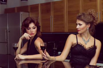 Two stylish rivals women in the kitchen and red wine
