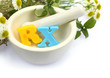 Mortar with fresh herbs and colorful letters RX