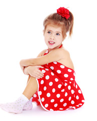 Pretty little girl sitting on the floor in a red dress with polk