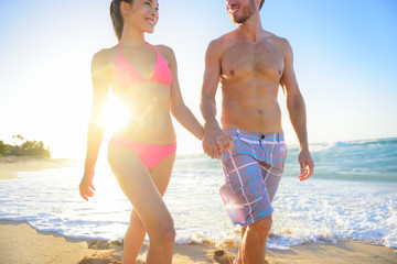 Attractive young couple walking on tropical beach