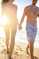 Couple walking on beach holding hands man smiling