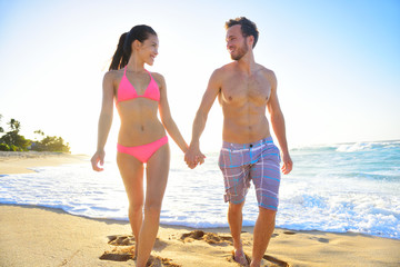 Couple romantic walking in beach sand holding hand