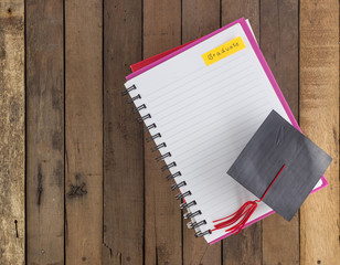 Graduation cap  on notebook  against wood background