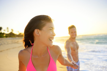 Romantic smiling young couple at beach in sunset