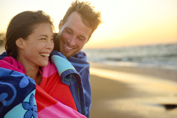 Romantic smiling mixed race couple on beach sunset