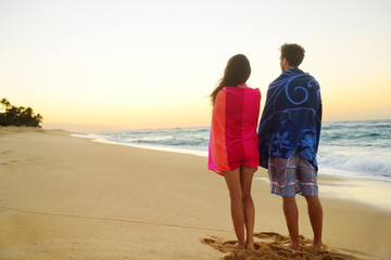 Young couple towels over shoulders in beach sand
