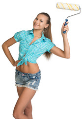 Pretty girl in shorts and shirt holding paint roller
