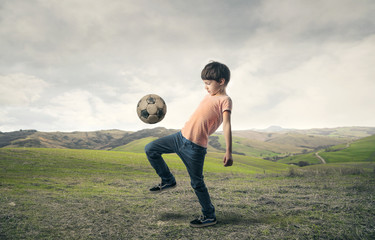 Boy playing football in the countryside