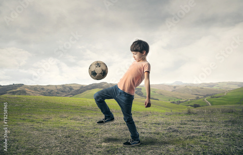 canvas print picture Boy playing football in the countryside