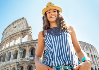 Portrait of happy young woman in front of colosseum in rome