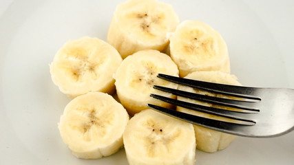 Slow motion mashing of cut pieces of banana into paste with fork