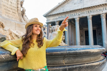 Young woman pointing near fountain of the pantheon in rome