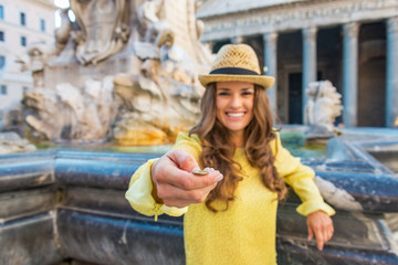 Closeup on young woman tossing coin near fountain  in Rome