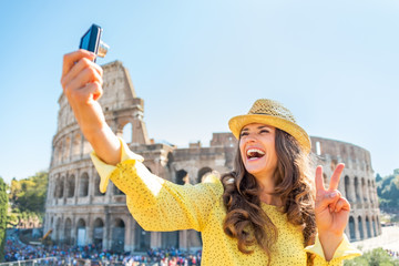 Happy young woman making selfie in front of colosseum in rome
