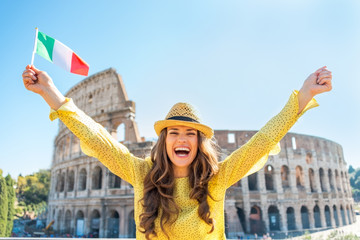 Portrait of happy woman rejoicing with italian flag in Rome