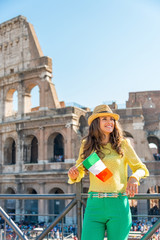 Happy young woman with italian flag in front of colosseum