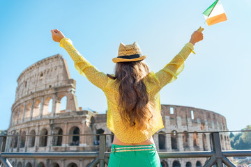 Young woman with italian flag rejoicing in front of colosseum