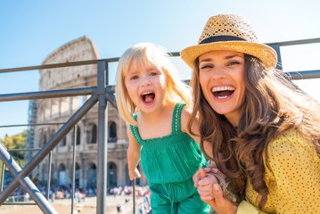 Portrait of happy mother and baby girl in front of colosseum