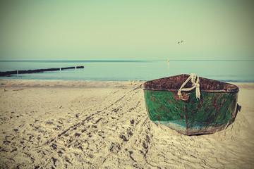Retro filtered picture of an old rusty steel boat on the beach.