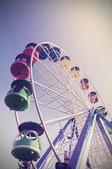 Retro filtered picture of ferris wheel in a park.