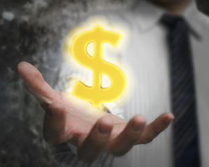 Glowing golden dollar sign in man's hand