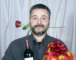 Man with beard holding wine present and one rose