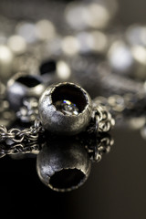 Close up of shiny beads attached by chains jewellry