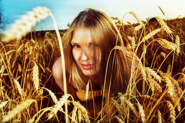 Pretty girl is looking out of the wheat field on the sunset back