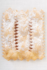 Chiacchiere, italian Carnival pastry on white tablecloth