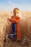 Little girl in a national Armenian dress costs among wheat field