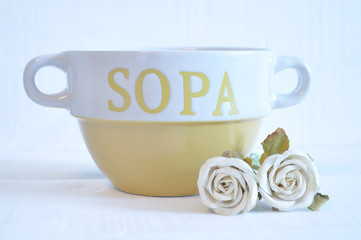 Empty soup yellow bowl with two artificial flowers