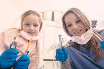 Little Female Dentists Holding Dental Tools Looking at Camera.