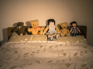 Teddies and Dolls on Bed