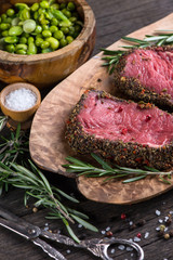 Top view on raw steak with herbs and pepper