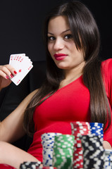 Girl in red dress holding Royal Flush, poker chips in foreground